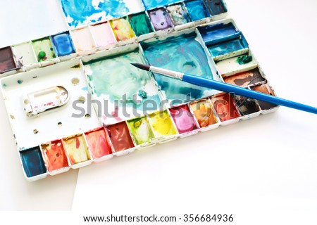 set of watercolor paints brushes for painting and blank white water color paper sheet of