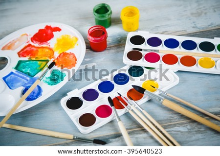 Set of watercolor paints, brushes for painting and palette on old vintage wooden background