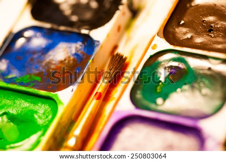 set of watercolor paints with brush, close up. shallow depth of field - stock photo