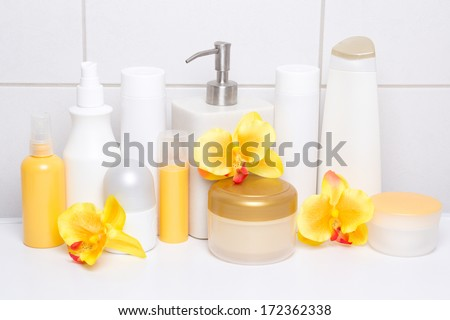 set of white cosmetic bottles and hygiene supplies with orange orchids over tiled wall in bathroom - stock photo