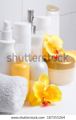 set of white cosmetic bottles with flowers over tiled wall - stock photo