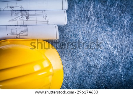 Set of white rolled up blueprints and construction helmet on metallic scratched background building and architecture concept. - stock photo