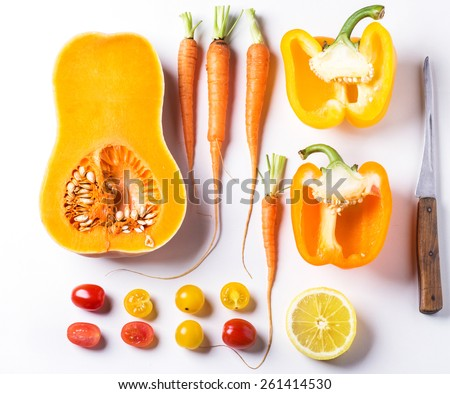 Set of whole and sliced red, orange and yellow vegetables over white background. Top view - stock photo