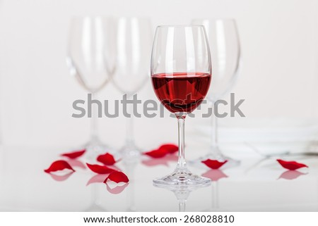 Set of wine glasses, red wine and rose petals - stock photo