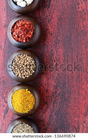 Set of wooden bowls with Indian spices - white cardamon, chili, coriander, yellow spicy nut mix and cumin, on rusted wooden background - stock photo