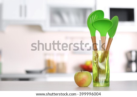 Set of wooden kitchen utensils in green glass pot with apple on the table - stock photo