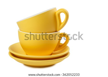 Set of yellow cups and saucers isolated on white
