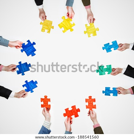 set painted puzzle pieces in people hands at four sides on grey background