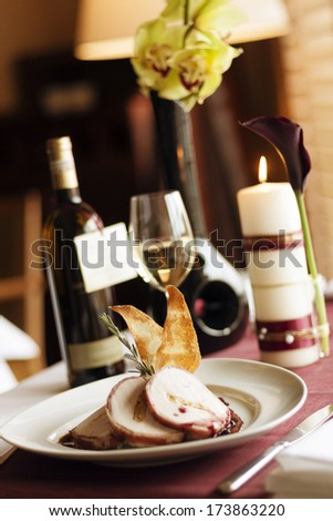 Set table. Cold cut meat on a decorated plate and bottle of wine in the background. - stock photo