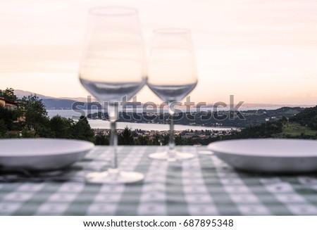Set table with empty glasses and plates on green and white table cloth with mountains and lake landscape as background at sunset