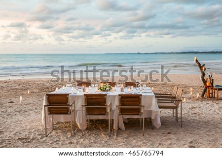 Set the table for dinner on the beach at sunset with golden light.