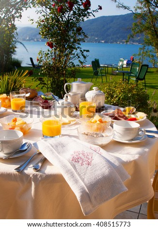 Set the table with breakfast on the green lawn in front of the lake