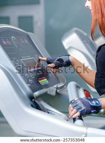 Set up the simulator. Sport and slender girl running on a treadmill. Athlete dressed in sports uniforms and running in the gym and customize simulator. - stock photo