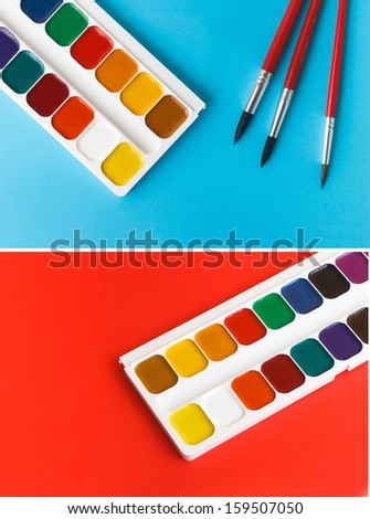 set watercolor paints for children on a red background - stock photo