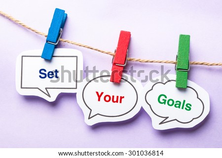 Set your goals paper bubbles with clip hanging on the line against purple background. - stock photo