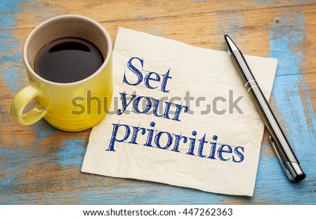Set your priorities reminder - handwriting on a napkin with a cup of espresso coffee