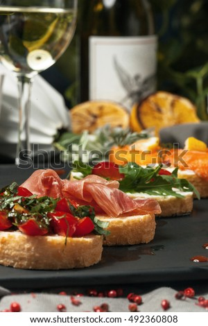 Seth bruschetta with fish, greens and meat with wine, feeding in the restaurant.