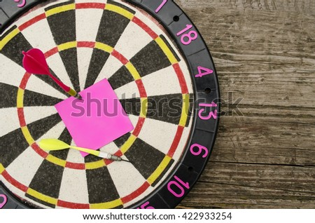 Setting and achieving goals: a dartboard with a blank note in the bulls-eye   - stock photo