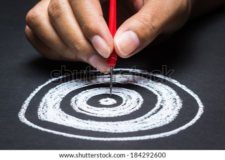 Setting goal or accurate planning, hand going to take dart into the center of sketching dartboard - stock photo