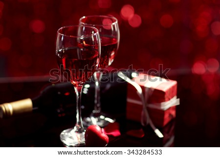 Setting of glasses with wine, bottle and a gift in the box, on red blurred background