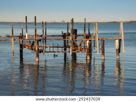 setting sun glow on old wooden dock slip - stock photo