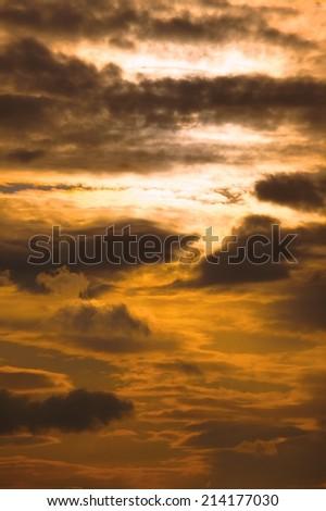 Setting sun in cloudy sky - stock photo