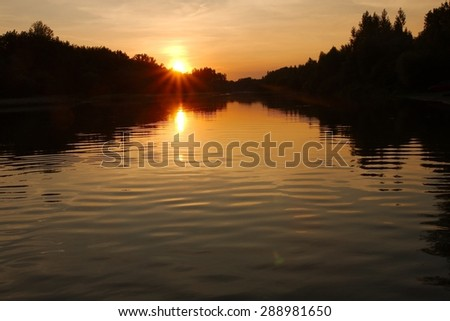 Setting sun in cloudy sky at the river - stock photo