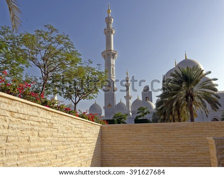 Setting sun view of a minaret and domes at the Sheikh Zayed Grand Mosque in Abu Dhabi, United Arab Emirates  - stock photo