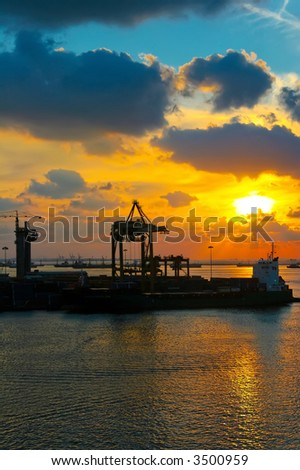 setting sun with a sea port crane - stock photo