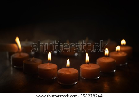 setting tealight candles in a shape of a heart, shallow focus photo