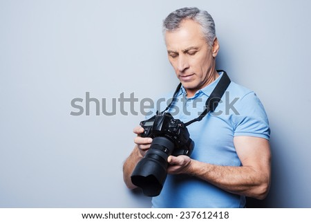 Setting the camera. Portrait of senior mature man in T-shirt holding camera while standing against grey background