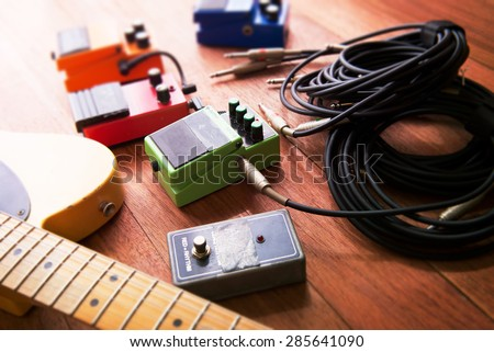 Setting up guitar audio processing effects. Electric guitar and stomp box type effectors and cables on studio floor. Intentionally shot with impressional feel, color and tone. - stock photo