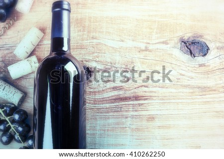 Setting with bottle of red wine, grape and corks. Wine list concept with copy space. Toned. - stock photo