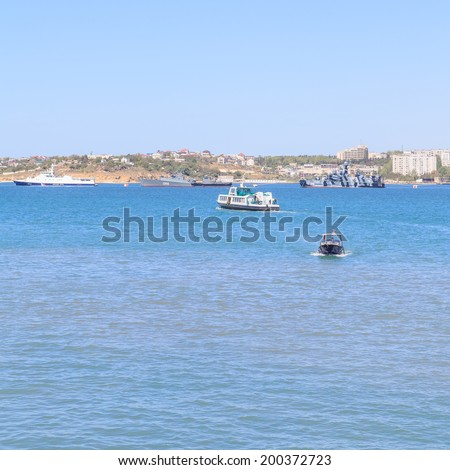 SEVASTOPOL, CRIMEA - MAY 7, 2014: Ships of Russian Navy Black Sea Fleet in harbor with ferry and touristic boats in the front