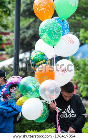 "SEVASTOPOL, RUSSIA - MAY 07: Celebrating the 69th anniversary of the Victory Day (WWII).Sevastopol 2014. Parade, boy selling holiday balloons with text: ""9 of May. We won!""  - stock photo"