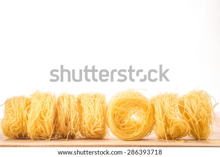 Seven balls of Angel's Hair spaghetti lie in a straight line on a wooden surface, in front of a white background. One ball of spaghetti faces forward. - stock photo