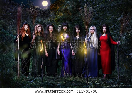 Seven beautiful witches with brooms in the night forest, standing in a row - stock photo