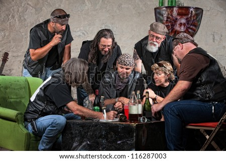 Seven biker gang members writing a plan indoors