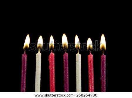 Seven burning birthday candles on black background  - stock photo