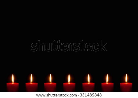 Seven burning candles in front of black background, copy space above the candles - stock photo