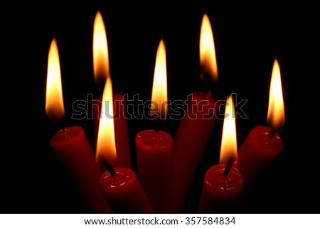 seven burning candles on black background