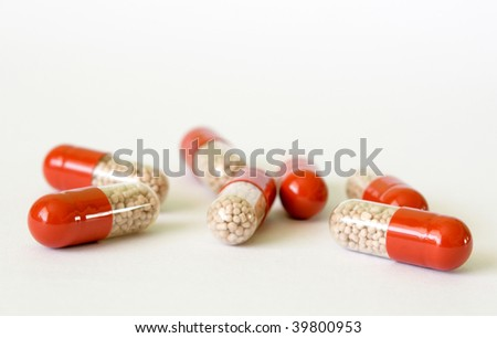 Seven capsules with transparent part and granules in site - stock photo