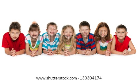 Seven children are lying on the floor on a white background