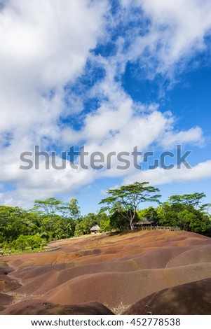 Seven Coloured Earth in Mauritius, Chamarel nature reserve. Green forest behind and blue cloudy sky