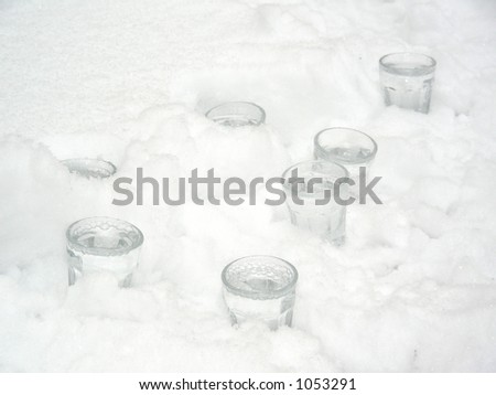 seven glasses of vodka in snow - stock photo