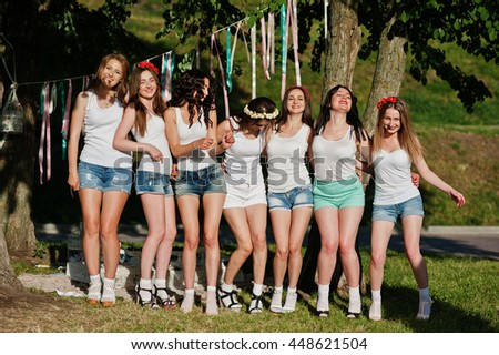 Seven happy and sexy girls on short shorts and white shirts posed at sunset park on bachelorette party