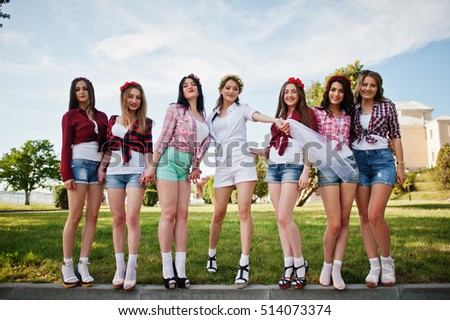 Seven happy and sexy girls on short shorts posed and having fun at park on bachelorette party