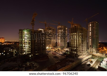 Seven high buildings under construction with cranes and illumination at dark night - stock photo