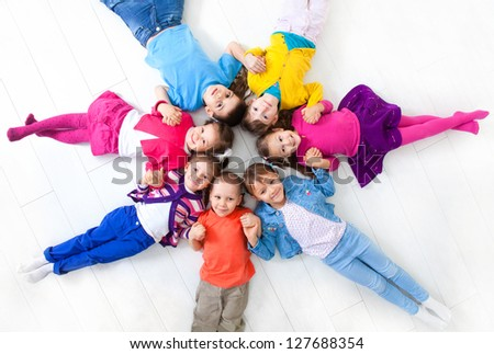 Seven kids are on the floor together. Top view - stock photo