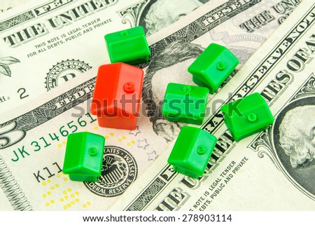 Seven little green and red houses made of plastic are laying on one dollar banknote - stock photo